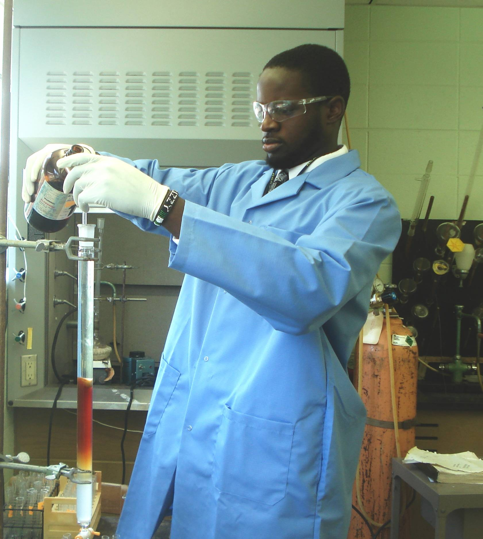 Man in blue labcoat pouring a container into a beaker
